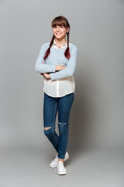 Retrato de corpo inteiro de uma estudante bonita sorridente Foto gratuita