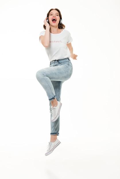 Retrato de corpo inteiro de uma garota excitada ouvindo música Foto gratuita