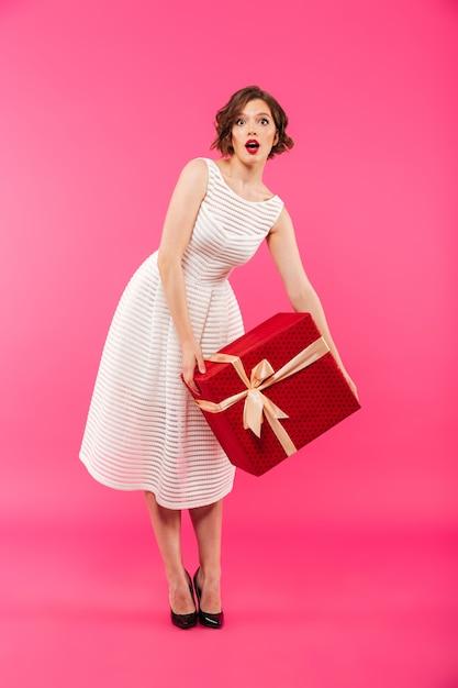 Retrato de corpo inteiro de uma garota surpresa, vestida de vestido Foto gratuita