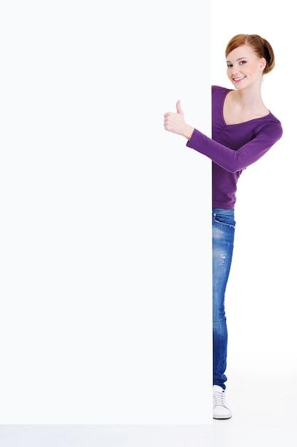 Retrato de corpo inteiro de uma jovem olhando para fora por causa de um outdoor vazio com sinal de positivo Foto gratuita