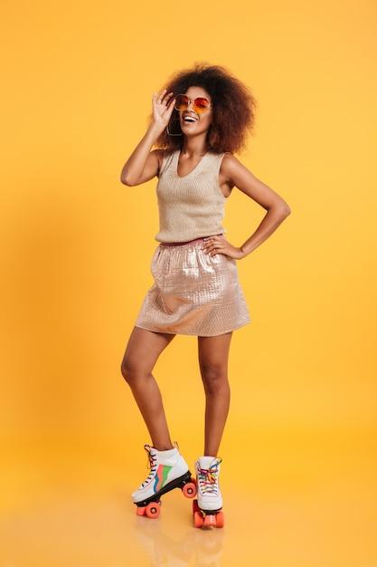 Retrato de corpo inteiro de uma mulher afro-americana feliz Foto gratuita