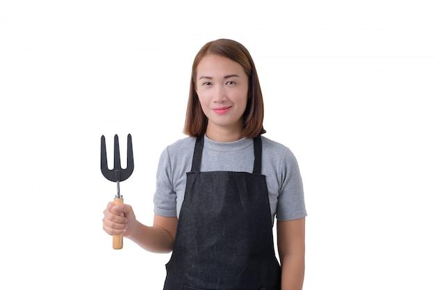 Retrato de corpo inteiro de uma mulher de trabalhador ou servicewoman na camisa cinza e avental está segurando a pá para cultivadores em fundo branco Foto Premium