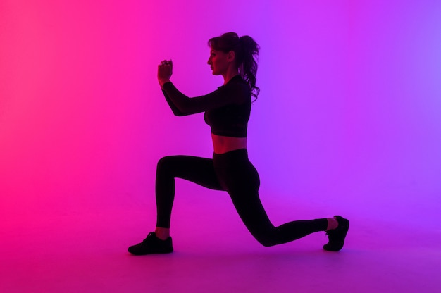 Retrato de corpo inteiro de uma mulher jovem fitness fazendo agachamento isolado em um fundo de cores vibrantes Foto Premium