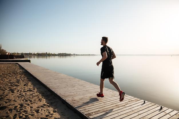 Retrato de corpo inteiro de vista traseira de um jovem esportista correndo Foto gratuita
