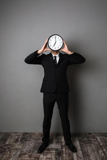 Retrato de corpo inteiro do empresário em terno preto, segurando o grande relógio na frente do rosto Foto gratuita