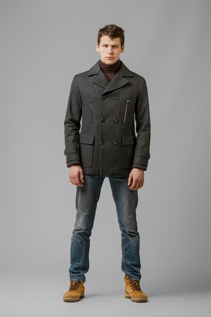 Retrato de corpo inteiro do homem bonito no casaco quente posando no estúdio Foto Premium