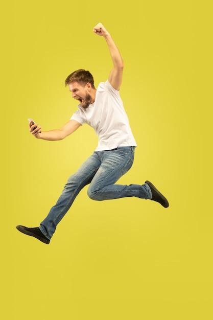 Retrato de corpo inteiro do homem pulando feliz isolado no amarelo Foto gratuita