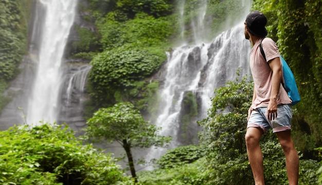 Retrato de corpo inteiro do jovem alpinista ou aventureiro em shorts jeans e snapback curtindo a natureza Foto gratuita