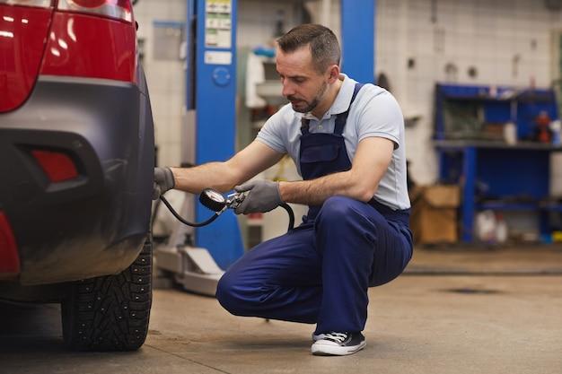 Retrato de corpo inteiro do mecânico de automóveis verificando a pressão dos pneus durante a inspeção do veículo na oficina, copie o espaço Foto Premium