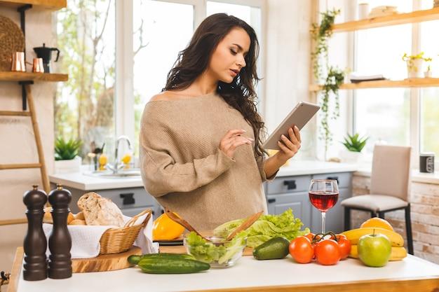 Retrato de cozinhar comida jovem saudável na cozinha, procurando uma receita na internet. usando computador tablet. Foto Premium