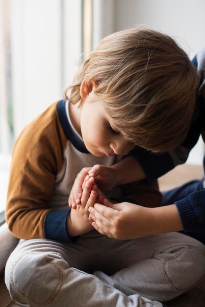 Retrato de criança adorável, aprendendo a rezar Foto gratuita