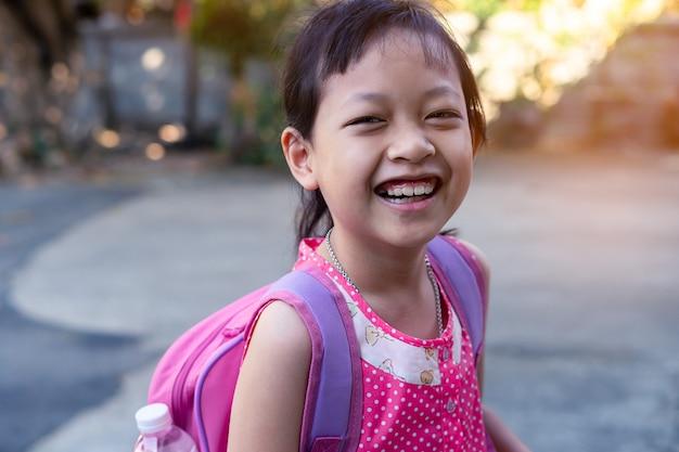 Retrato de criança asiática sorridente feliz menina com mochila Foto Premium