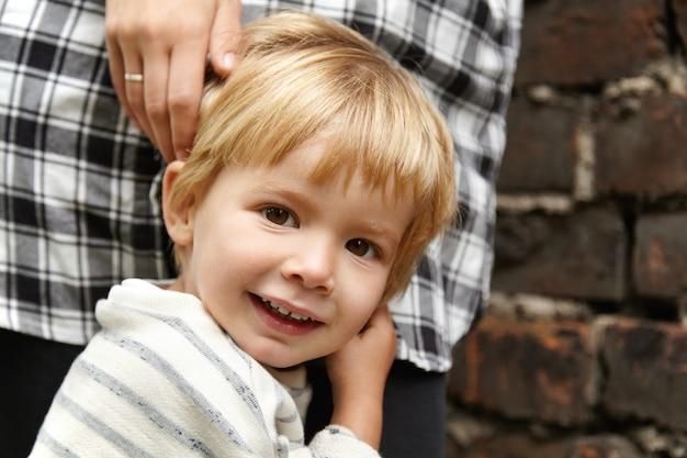 Retrato de criança feliz andando com a mamãe na rua. garoto sorridente do sexo masculino com olhos castanhos, cabelo loiro. ele se sente seguro porque a mãe está perto dele, pronta para protegê-lo. Foto gratuita