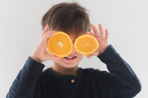 Retrato, de, criança, segurando, laranja metades, sobre, olhos Foto gratuita
