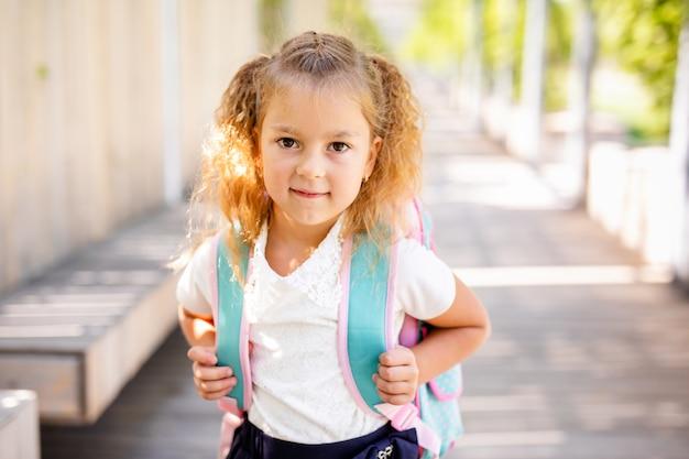 Retrato de crianças em idade escolar correndo no caminho no parque (foco na menina) Foto Premium