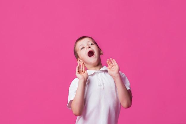 Retrato, de, cute, menino, gritando, com, boca aberta, ligado, cor-de-rosa, fundo Foto gratuita