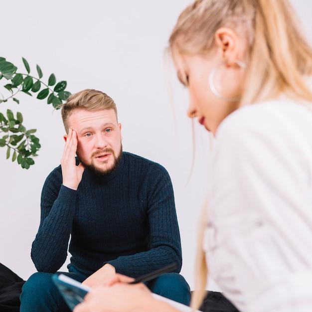 Retrato, de, deprimido, macho, paciente, falando, com, femininas, psicólogo Foto gratuita