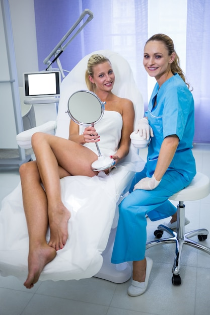 Retrato de dermatologista e paciente sorrindo para a câmera Foto gratuita
