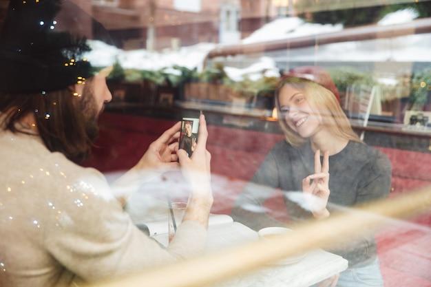 Retrato de descolados haapy no café por trás do vidro Foto gratuita