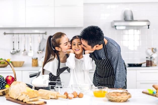 Retrato de desfrutar de amor feliz pai e mãe de família asiática com filha pequena menina asiática se divertindo cozinhando junto com assar biscoitos e ingredientes do bolo na mesa da cozinha Foto Premium
