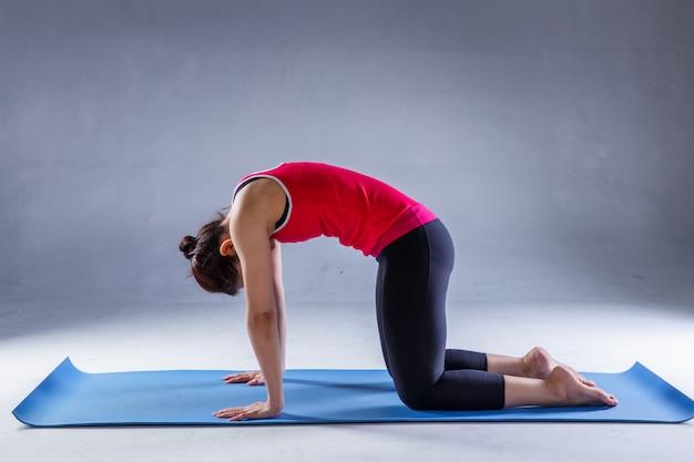 Retrato, de, deslumbrante, mulher jovem, prática, ioga, em, estúdio, ligado, experiência escura Foto Premium