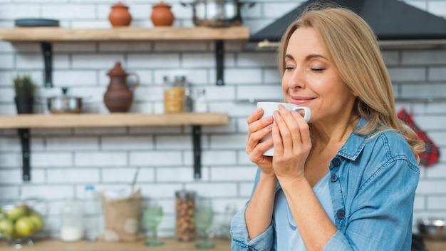 Retrato, de, deslumbrante, senhora sorridente, cheirando, e, café bebendo, de, copo, em, a, cozinha Foto gratuita
