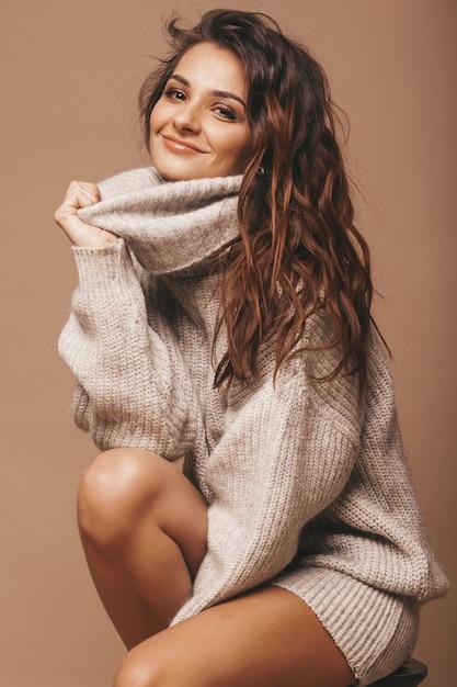 Retrato de doce doce bonito mulher morena sorridente. garota de suéter cinza casual. modelo posando no estúdio. sentado na cadeira Foto gratuita