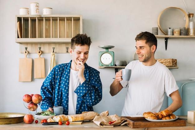 Retrato, de, dois, feliz, homem jovem, preparando café da manhã, em, cozinha Foto gratuita