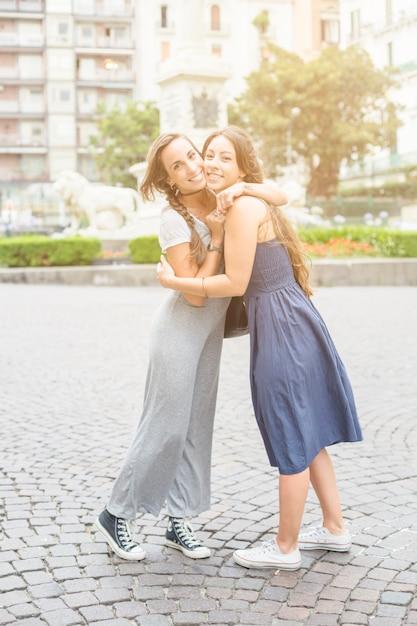 Retrato, de, dois, femininas, amigos, embracing, outro, ficar, ligado, pavimento Foto gratuita