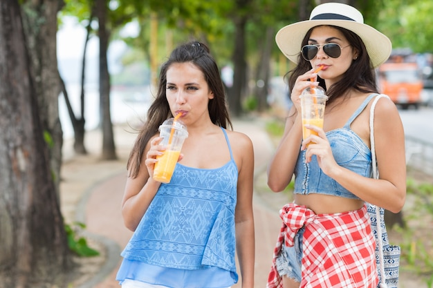 Retrato, de, dois, mulher bonita, bebendo, suco fresco, enquanto, passeio Foto Premium