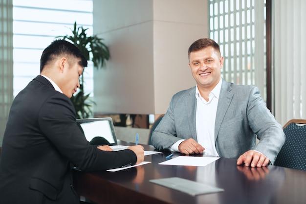 Retrato de dois parceiros de negócios, sentado em uma mesa juntos e trabalhando. Foto Premium