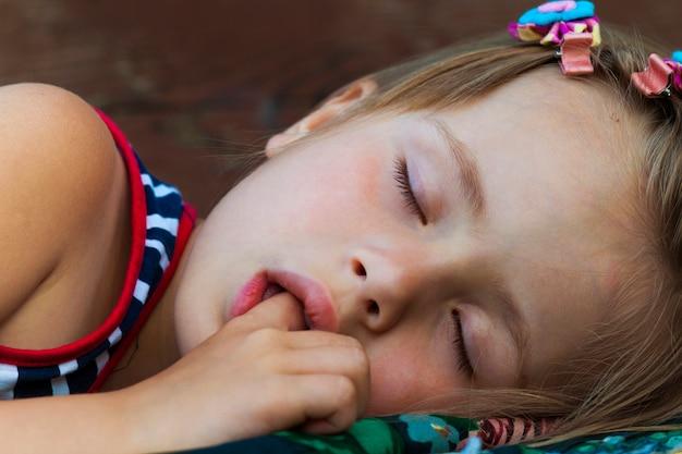 Retrato de dormir menina criança bonita que chupa o dedo enquanto dorme. Foto Premium