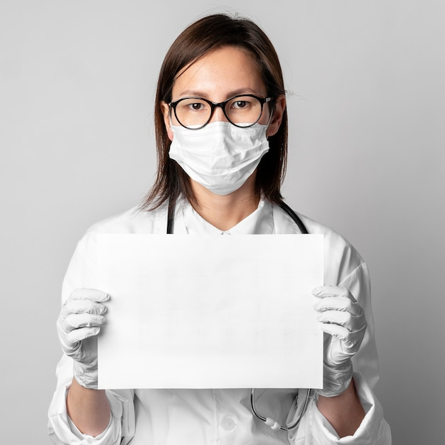 Retrato, de, doutor, com, máscara cirúrgica, segurando papel Foto gratuita