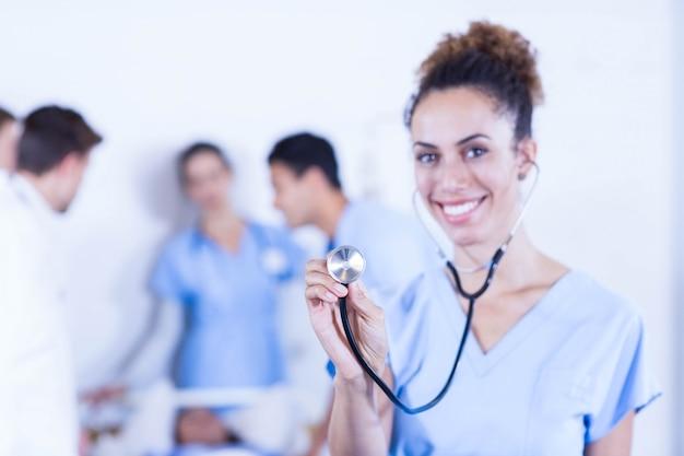 Retrato, de, doutores, ficar, com, braços cruzaram, e, outro, doutor, examinando, um, paciente, atrás de, hospitalar Foto Premium