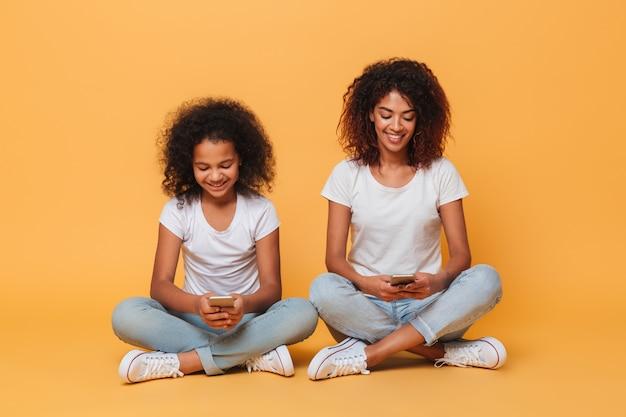 Retrato de duas irmãs afro-americanas alegres Foto gratuita