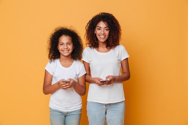 Retrato de duas irmãs afro-americanas felizes com smartphones Foto gratuita