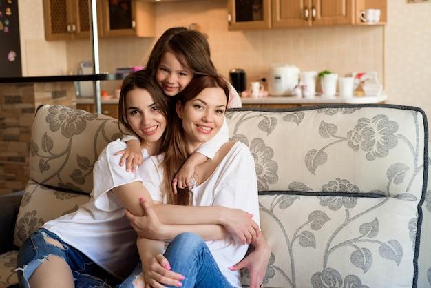 Retrato de duas irmãs e uma menina sentada no sofá, sorrindo. Foto Premium