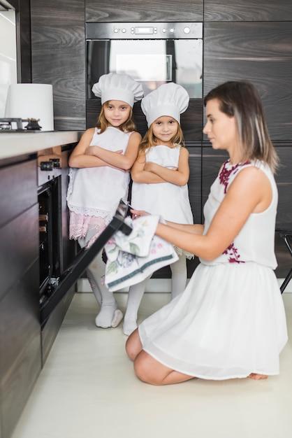 Retrato, de, duas irmãs, posar, em, cozinha, enquanto, mãe, pôr, biscoitos, em, forno Foto gratuita