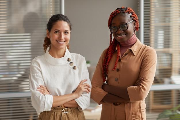 Retrato de duas jovens empresárias de sucesso sorrindo para a câmera enquanto posam de pé com os braços cruzados no escritório, copie o espaço da cintura para cima Foto Premium