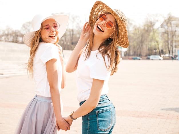 Retrato de duas meninas de hipster loira sorridente jovem bonita em roupas de camiseta branca na moda verão. . modelos positivos, segurando um ao outro mão Foto gratuita
