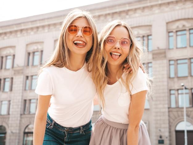 Retrato de duas meninas de hipster loira sorridente jovem bonita em roupas de camiseta branca na moda verão. mulheres despreocupadas sexy, posando na rua. modelos positivos mostrando a língua, em óculos de sol Foto gratuita