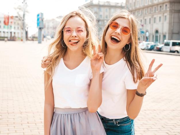 Retrato de duas meninas de hipster loira sorridente jovem bonita em roupas de camiseta branca na moda verão. mulheres despreocupadas sexy, posando na rua. modelos positivos mostrando língua e sinal de paz Foto gratuita