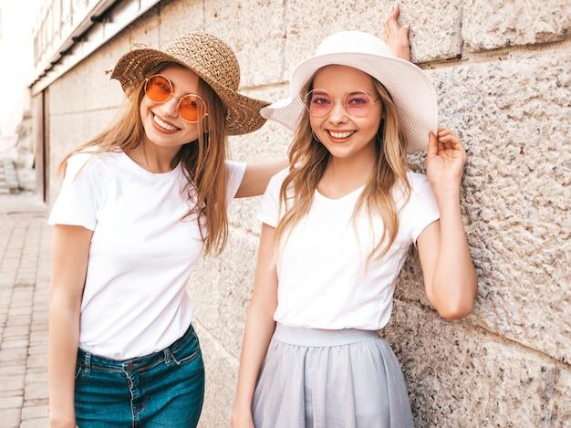 Retrato de duas meninas de hipster loira sorridente jovem bonita em roupas de camiseta branca na moda verão. Foto gratuita