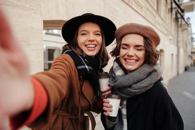Retrato de duas meninas felizes, vestidas com roupas de outono Foto gratuita