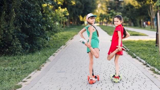 Retrato, de, duas meninas, ficar, um pé, sobre, a, pontapé scooter, parque Foto gratuita