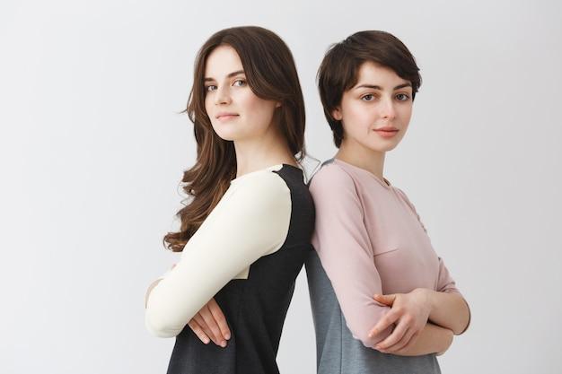 Retrato de duas meninas lésbicas com cabelos escuros, sorrindo, de costas para o outro, cruzando as mãos, posando para o artigo sobre a vida de gays. Foto gratuita