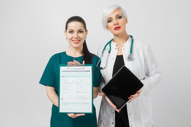 Retrato de duas mulheres jovens em traje de médicos isolado na Foto Premium