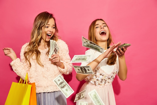 Retrato de duas mulheres loiras sorridentes elegantes jovens segurando sacolas de compras. mulheres vestidas com roupas de verão hipster. modelos positivos gastando dinheiro na parede rosa Foto gratuita