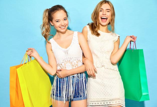 Retrato de duas mulheres loiras sorridentes elegantes jovens segurando sacolas de compras. mulheres vestidas com roupas de verão hipster. positivos modelos posando sobre parede azul Foto gratuita