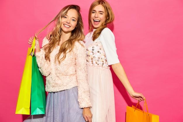 Retrato de duas mulheres loiras sorridentes elegantes jovens segurando sacolas de compras. mulheres vestidas com roupas de verão hipster. positivos modelos posando sobre parede rosa Foto gratuita